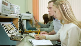 Attractive young blonde woman is studying at university as an engineer. Together with the young man write down the. Readings on laboratory work stock video