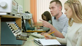 Attractive young blonde woman is studying at university as an engineer. Together with the young man write down the. Readings on laboratory work stock video footage