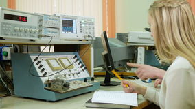 Attractive young blonde woman is studying at university as an engineer. Together with the young man write down the. Readings on laboratory work stock footage
