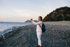 Attractive young blonde woman tourist making photo an retro camera on beach Stock Photos