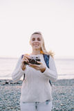 Attractive young blonde woman tourist standing with an retro camera in hands on a background of sea Royalty Free Stock Images