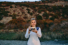 Attractive young blonde woman tourist standing with an retro camera in hands outdoor Royalty Free Stock Image