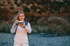 Attractive young blonde woman tourist standing with an retro camera in hands outdoor Royalty Free Stock Images