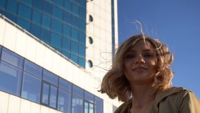 Attractive Young Blonde Woman in Trench and High Heel Shoes with Vintage Suitcase on the Marine Station, with High Blue. Glass Hotel on Background. Slow Motion stock video