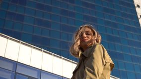 Attractive Young Blonde Woman in Trench and High Heel Shoes with Vintage Suitcase on the Marine Station, with High Blue. Glass Hotel on Background. Slow Motion stock video footage