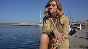 Attractive Young Blonde Woman in Trench with Vintage Suitcase is Sitting on the Jacht Pier and Looking in the Sea. Attractive Young Blonde Woman in Trench and stock video footage
