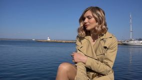 Attractive Young Blonde Woman in Trench with Vintage Suitcase is Sitting on the Jacht Pier. Attractive Young Blonde Woman in Tranch and High Heel Shoes with stock video
