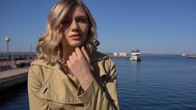 Attractive Young Blonde Woman in Trench with Vintage Suitcase is Sitting on the Jacht Pier. Attractive Young Blonde Woman in Tranch and High Heel Shoes with stock video footage
