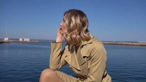 Attractive Young Blonde Woman in Trench with Vintage Suitcase is Sitting on the Jacht Pier. Parallax. Attractive Young Blonde Woman in Tranch and High Heel Shoes stock video footage