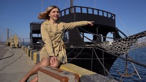 Attractive Young Blonde Woman in Trench with Vintage Suitcase is Sitting on the Jacht Pier and Points in the Sea. Dark. Attractive Young Blonde Woman in Tranch stock footage