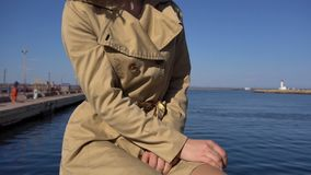 Attractive Young Blonde Woman in Trench with Vintage Suitcase is Sitting on the Jacht Pier, Tilt Up and closing Frame. Attractive Young Blonde Woman in Tranch stock video footage