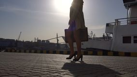 Attractive Young Blonde Woman in Trench with Vintage Suitcase Walking on the Marine Station. Attractive Young Blonde Woman in Tranch and High Heel Shoes with stock video