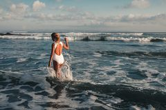 Attractive young blonde woman walking at beach stock photography