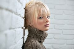 Gogeous blonde model posing sensually. Attractive young blondie posing at home near the brisck wall wearing wark winter sweater looking to the camera seriously Stock Photography