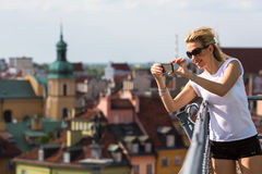 Attractive young blondie woman taking pictures on phone from lookout tower Castle Square in Warsaw. Stock Image