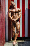 Attractive young bodybuilder against striped beach changing room Royalty Free Stock Photos