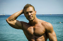 Attractive young bodybuilder getting out of sea or ocean Stock Photos