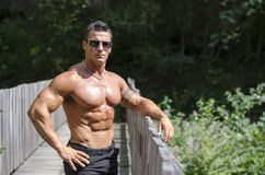 Attractive young bodybuilder outdoors, leaning Stock Images