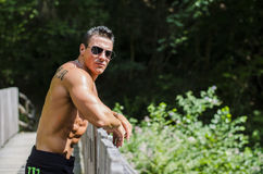 Attractive young bodybuilder outdoors, leaning Royalty Free Stock Photography