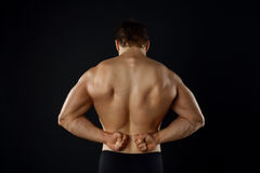 Attractive young bodybuilder is presenting his Royalty Free Stock Photo