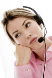 Attractive Young Bored Business Woman Using a Telephone Headset. DSLR royalty free digital image of an attractive young Caucasian woman in her late twenties stock photos
