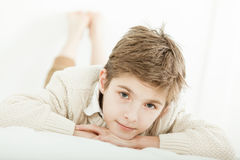 Attractive young boy relaxing on his bed Stock Images
