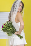 Attractive Young Bride Holding Bouquet of Flowers Behind Her Back Stock Photo