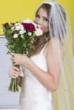 Attractive Young Bride Holding Wedding Flowers Smelling them Royalty Free Stock Image