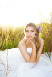 Attractive Young Bride Sitting In The Grass Stock Image