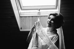 Wedding dress embroidered with crystals and pearls hangs over th. Attractive young bride is smiling holding wedding dress Royalty Free Stock Images