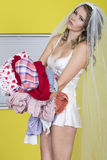 Attractive Young Bride to Be Carrying Holding Dirty Laundry. Beautiful Young Bride to be Carrying colourful Laundry, in despair of having to do chores or Royalty Free Stock Image