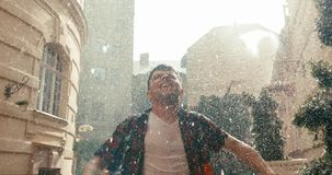 Attractive young brunet is raising up hands and shouting while enjoying the rain during the sunny day.