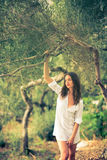 Attractive, young brunette on the beach, amid olive trees Stock Photos