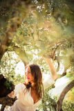 Attractive, young brunette on the beach, amid olive trees Stock Photo
