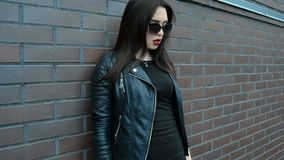 Attractive young brunette in black clothes and sunglasses stands near a wall and posing one camera stock video