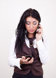 Attractive young brunette calling by mobile. Attractive young businesswoman with two phones in working process Royalty Free Stock Images