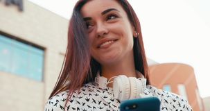 Attractive young brunette with charming smile is browsing and texting via the mobile phone. Up close-up portrait. 4k. Footage stock video