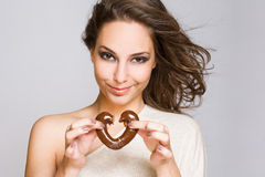 Attractive young brunette with chocolate heart. Stock Photo