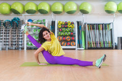 Attractive young brunette female athlete doing advanced split stretching exercise for legs smiling looking at camera Royalty Free Stock Photography
