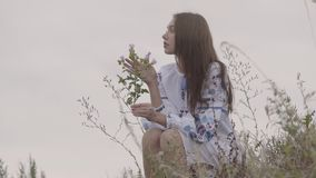 Attractive young brunette girl in long embroidered dress holding the wild flower in hands. The girl touching the violet. Attractive young brunette girl in long stock footage