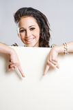 Attractive young brunette holding blank billboard. Stock Image
