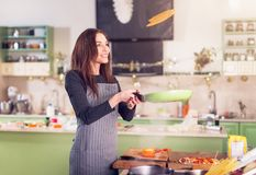 Attractive young brunette housewife in casual clothes and apron tossing pancakes on pan in the kitchen Stock Image