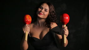 Attractive young brunette musician playing red maracas stock video footage