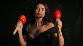 Attractive young brunette musician playing red maracas stock video
