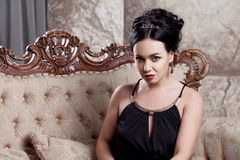 Attractive young brunette sitting on  beautiful Royalty Free Stock Image
