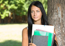 Attractive young brunette student outdoors. Stock Photos