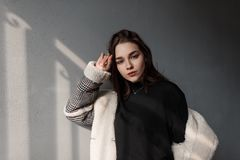 Attractive young brunette woman in a black stylish shirt in a fashionable plaid jacket with white fur is enjoying the bright sun. On a spring day. Beautiful royalty free stock images