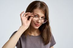 Attractive young brunette woman corrects her glasses and looks attentively at the camera. Large horizontal portrait Stock Photos