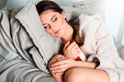 Attractive young brunette woman in home bathrobe, fell asleep on Stock Photos