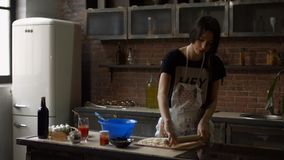 Cheerful woman kneading dough in the kitchen stock video